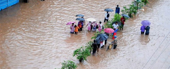 Guwahati: People  make their way through a flooded street after heavy rainfall in Guwahati, Assam on Tuesday. PTI Photo(PTI6_13_2017_000183B)